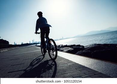 cyclist riding bike in the sunrise coast road