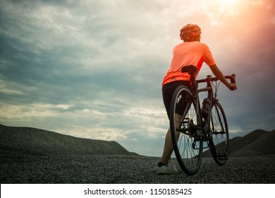 cyclist riding bike in the sunrise path