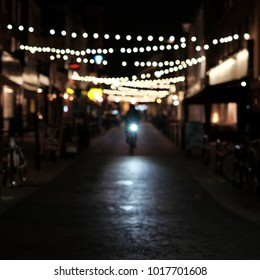 Cyclist riding down cobbled street in London with decorative lighting in background.