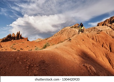 "Cyclist riding a mountain bike downhill style in a canyon ""Skazka"" that looks like a Martian landscape. Issyk-Kul, Kyrgyzstan."