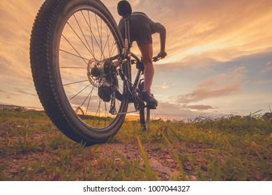 Cyclist riding mountain bike on  trail at sunrise