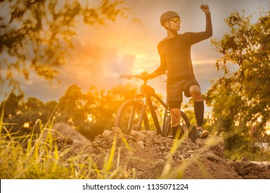 Cyclist riding mountain bike on trail at sunrise