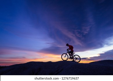 Cyclist riding mountain bike on the rocky trail at sunset.