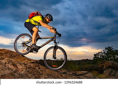 Cyclist Riding the Mountain Bike on the Rocky Trail at Sunset. Extreme Sport and Enduro Biking Concept.