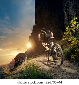 Cyclist riding mountain bike on trail at evening.