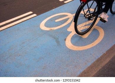 Cyclist riding on blue bicycle lane top shot close up of rear of bicycle in copenhagen with bicycle graphic on floor