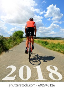 Cyclist riding on a road bike in the rural landscape. Forward to the New Year 2018.