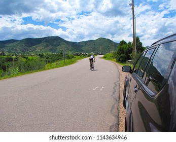 A cyclist riding up a steep hill in the Clear Creek Canyon in Colorado on a summer day