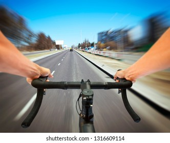 The cyclist is riding through the the asphalt road