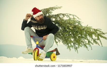 Cyclist in santa hat and sporty wear on winter day. Christmas and new year. Hipster carrying xmas tree and axe on white snow. Man riding tricycle on snowy landscape. Holiday celebration concept.