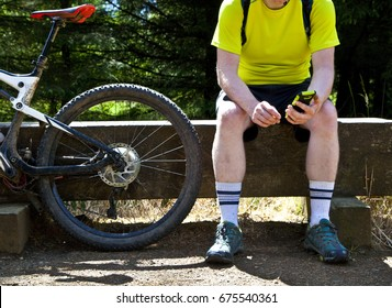 Cyclist sat on a bench next to a bike looking at a phone