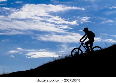cyclist silhouette in blue sky, clouds, mountain bike