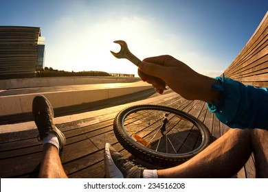 cyclist sitting and resting with the wrench in his hand and the mountain bike wheel at the sunset, POV view