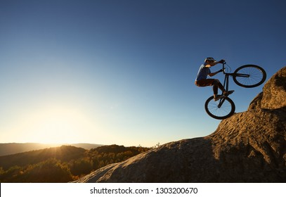 Cyclist standing on back wheel on trial bike. Professional sportsman rider making acrobatic stunt on the edge of big boulder on the top of mountain at sunset. Concept of extreme sport active lifestyle