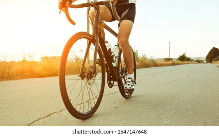 The cyclist is training on his road bike outside the city by asphalt road