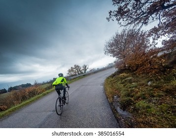 cyclist trains along a mountain road during a storm. Low angle.