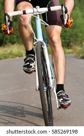 cyclist trains young male in a sports bike. cyclist feet on the pedals.