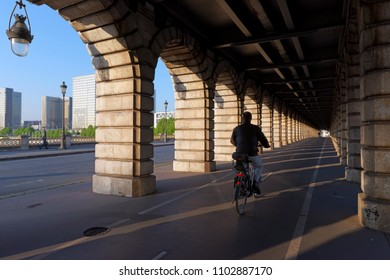 Cyclist under the archs of the Bercy bridge