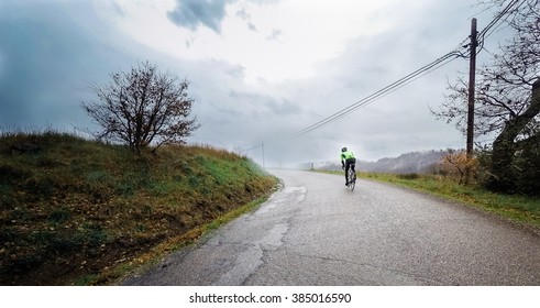 Cyclist in an uphill road during a storm. POV Original point of view