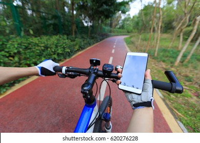 Cyclist use smartphone for navigation when riding mountain bike on forest trail