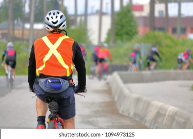 A cyclist wears brightly colored safety apparel to help increase visibility while he's cycling.