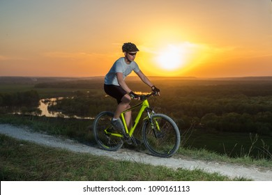 A cyclist in a white T-shirt rides a bike along the mountain path. The concept of extreme sports. Mountain bike.