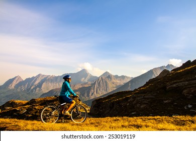Cyclist woman on the top of  height mountains, Dolomites, Italy