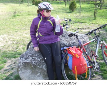 A cyclist women  with  a bike and a rock ana a bottle of water in a park