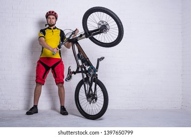 A cyclist in a yellow T-shirt and red shorts is holding a mountain bike against the background of a white wall, free space. Full suspension. Active lifestyle, cycling.
