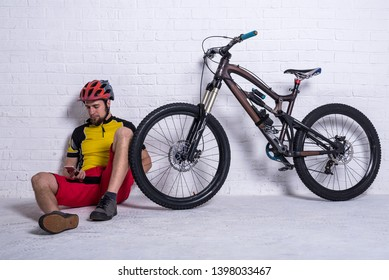 Cyclist in a yellow T-shirt and red shorts sitting next to a mountain bike and talking on a smartphone against the background of a white wall, free space. Full suspension. Active lifestyle, cycling.