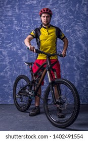 Cyclist in a yellow T-shirt and red shorts is holding a mountain bike against the background of a blue wall. Full suspension. Active lifestyle, cycling.