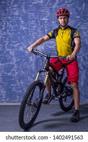 Cyclist in a yellow T-shirt and red shorts is sitting on a mountain bike against the background of a blue wall. Full suspension. Active lifestyle, cycling.