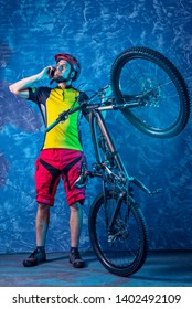 Cyclist in a yellow T-shirt and red shorts is holding a mountain bike against the background of a blue wall and talking on the smartphone. Full suspension. Active lifestyle, cycling.