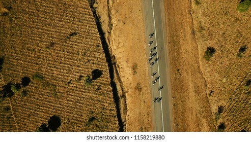 Cyclists birds eye view termac road dry with fields in Malawi Africa