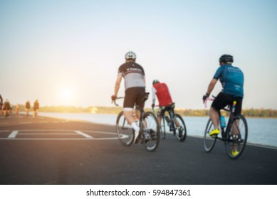 The cyclists blurred photo on road background on sunset