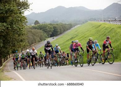 Cyclists Chonburi - JUNE 30 2017 Group Of Cyclists or Bicycle club cycling uphill along slope road of Bangpra reservoir  , Bangpra , Sriracha province, Thailand