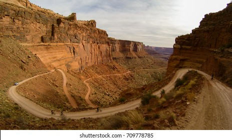 cyclists climb a winding dirt road up the steep cliff of Canyonlands national park