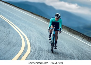 Cyclists are cycling, climbing up to the top.