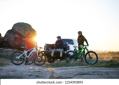 Cyclists Friends are Resting on the Pickup Offroad Truck after Bike Riding in the Mountains at Warm Autumn Sunset. MTB Adventure and Car Travel Concept.