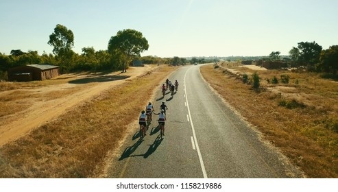 Cyclists high-five on stretched long tarmac road in Malawi Africa