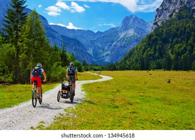 Cyclists on Alps mountains landscape background.