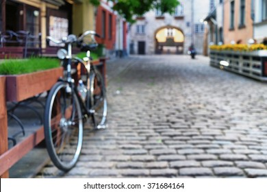 Cyclists at the outdoor cafe with flowers and green grass in the old city of Riga on the street with cobblestones in the summer day. Blurry