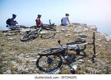 Cyclists are resting on a cliff. Three cyclist are resting on the top of the mountain Ai-Petri in Crimea. They admire the seascape from a height. Bicycles in the foreground.