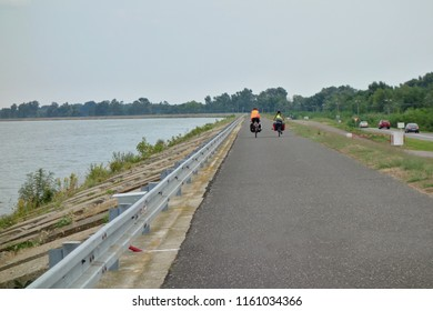 Cyclists ride along the cycle path along the Danube river, water dam Gabcikovo. Europe, Slovakia, the city of Bratislava. Cycling concept, cyclist rides a bicycle.