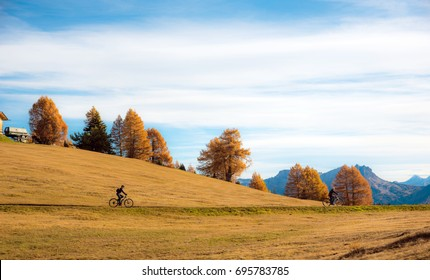 Cyclists ride road in Alps fall in Alpe di Siusi. Dolomites, South Tyrol, Alps, Italy. (active lifestyle, bicycle, travel, holiday, inner peace, harmony, honeymoon - concept)