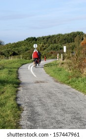 Cyclists riding along cycle path near Vuurtoren sand dunes, Holland