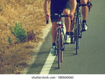 Cyclists riding a bicycle on the road.