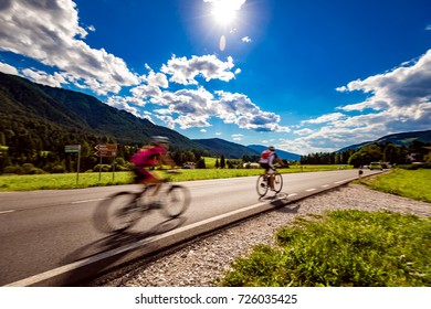 Cyclists riding a bicycle on the road in the background the Dolomites Alps Italy. Warning - authentic shooting there is a motion blur.