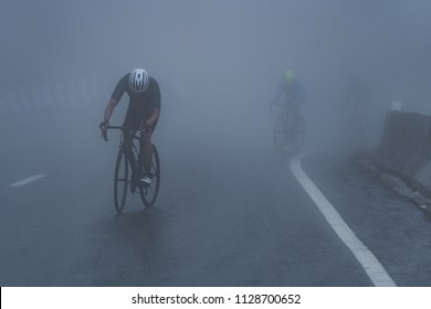 Cyclists are riding their bike up high on hill through a mist. Morning ride in a bad weather day: fog, rain, wind and cold day.