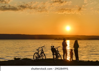 Cyclists at the river at sunset